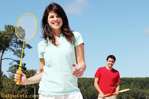 Молодая семейная пара вдвоем играет в бадминтон.