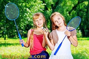 Бадминтон - игра на двоих. Девочки с ракетками и  воланом.