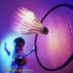 Игрок в бадминтон отбивает летящий воланчик центральной частью ракетки.