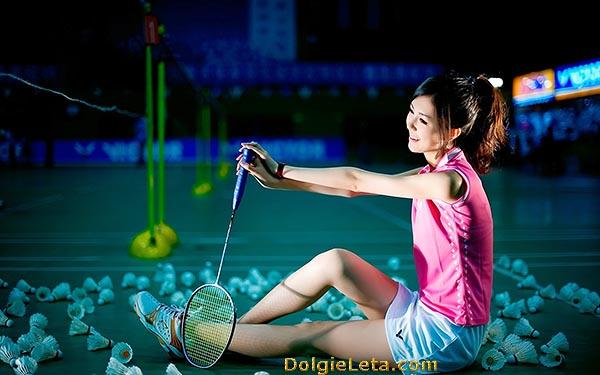 Игра спортивный бадминтон - на фото девушка отдыхает после занятий в окружении воланчиков.