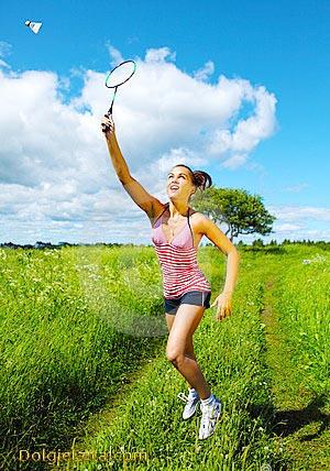 Девушка на природе играет в бадминтон, отбивая ракеткой летящий воланчик.