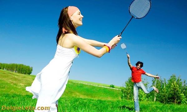 Молодая пара на природе весело с настроением играет в бадминтон.