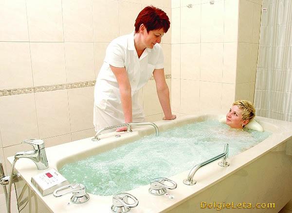 Женщина принимает процедуру хвойно-жемчужную ванну под присмотром и рекомендациями врача.