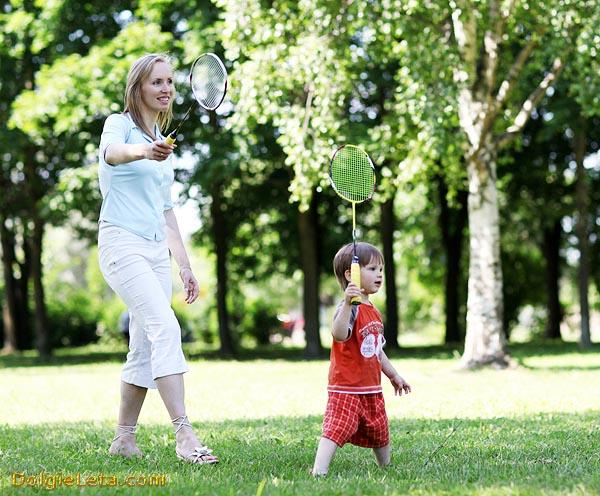 Мама с малышом на природе на улице играют в бадминтон.
