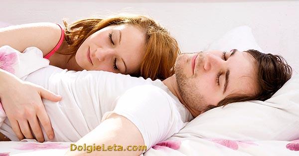 Молодая семейная пара сладко спит обнявшись друг с другом.