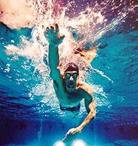 Пловец плывет в бассейне техникой и стилем кроль.