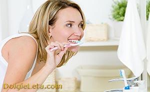 Женщина перед зеркалом отбеливает зубы в домашних условиях.