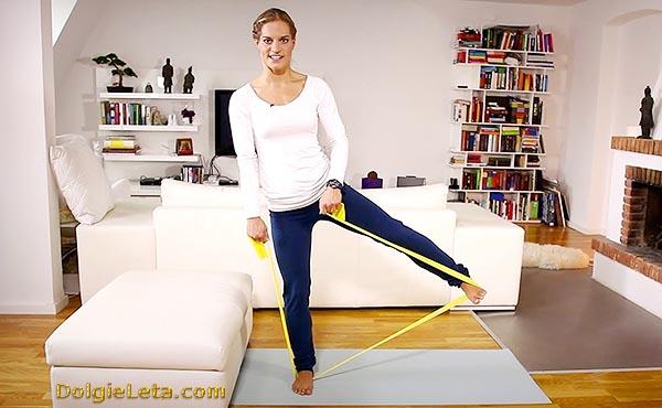 Девушка занимается с эспандером эластичной лентой в домашних условиях - упражнения для ног.