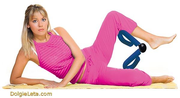 Девушка выполняет упражнения для ног с эспандером бабочка.