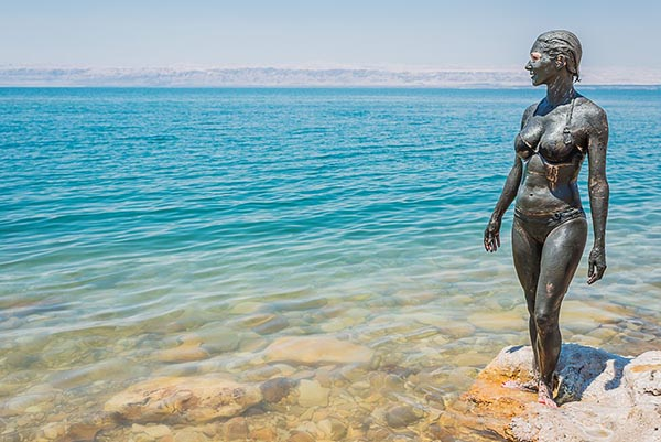 Женщина на берегу Мертвого моря обмазана лечебными грязями.