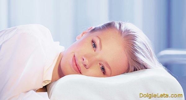 На фото девушка в прекрасном настроении лежит головой на лечебной ортопедической подушке.