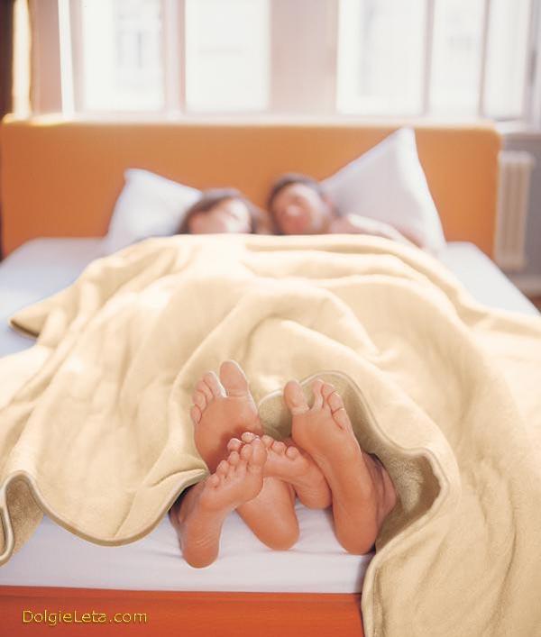 На фотографии семейная пара лежит под двуспальным электроодеялом.