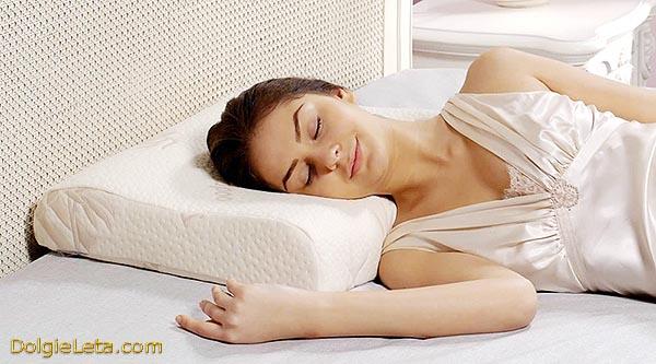Женщина спит на ортопедической подушке под головой.