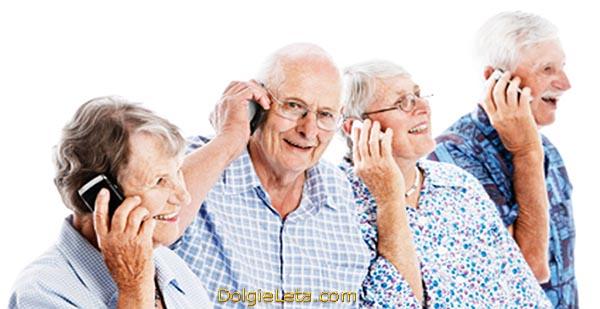 Пожилые люди с улыбками и хорошим настроением разговаривают по мобильным телефонам.