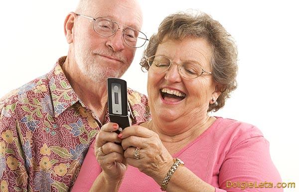 Пожилая семейная пара в прекрасном настроении и с улыбками общается по сотовому телефону.