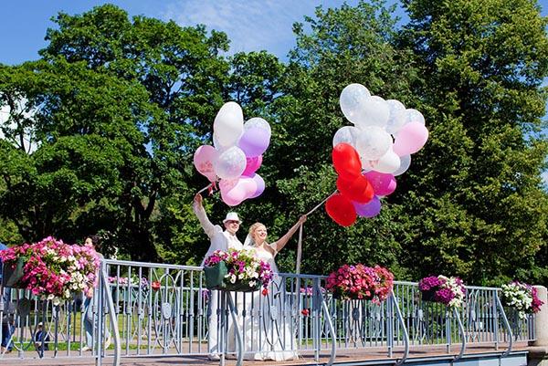 Фотография молодоженов с воздушными шарами на мосту в Таврическом саду.