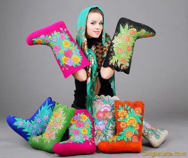 На студийном фото девушка демонстрирует расписные цветные дизайнерские валенки.