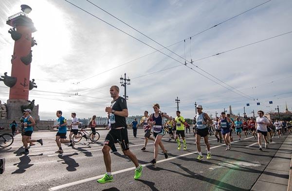 На фотографии спортсмены пробегают Стрелку Васильевского острова в Санкт-Петербурге.