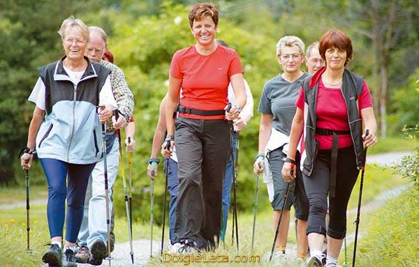 Польза скандинавской ходьбы с палками - на фото тренируется группа людей различного возраста.
