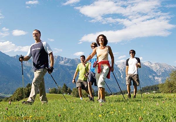 Отзывы о скандинавской ходьбе с палками - на фото группа людей идет по полю на фоне гор.