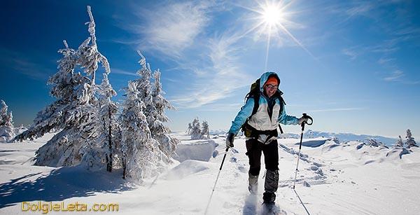 На фотографии женщина занимается скандинавской финской  ходьбой с палками зимой по заснеженным горам.