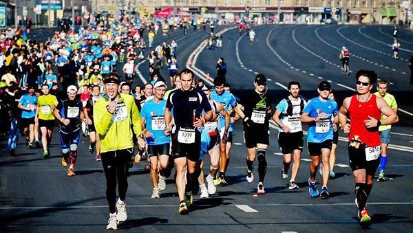 Спортсмены и участники московского марафона бегут по проспекту в Москве