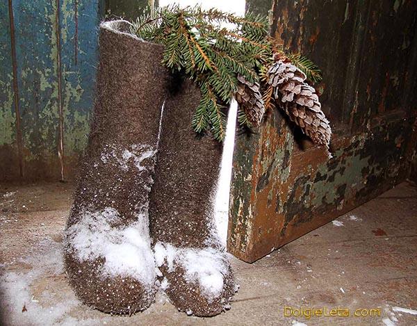 Художественное фото простых обычных заснеженных валенок с еловой веткой в деревенском доме.