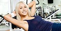 Девушка занимается в спортивном зале физическими упражнениями.