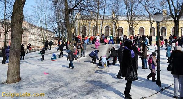 Детишки и родители зимой катаются с ледяной горки  в Юсуповском саду.