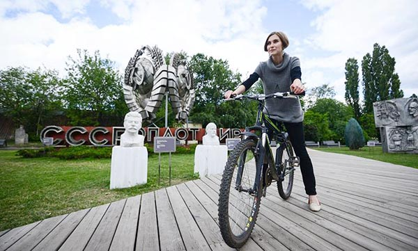 Девушка на велосипеде в парке искусств Музеон в Москве.