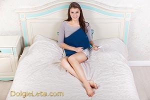 Девушка с электрогрелкой сидит на кровати.