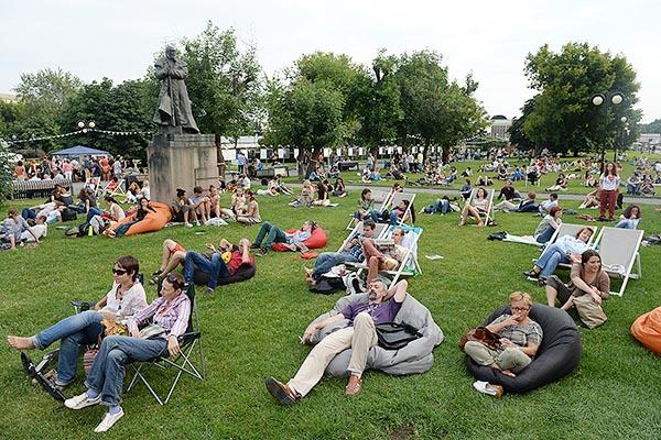 На фото люди отдыхают на траве в парке Музеон.