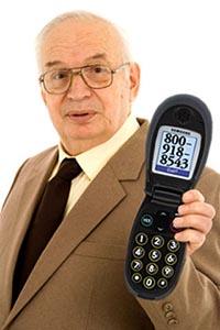 На фото пожилой мужчина держит в руках телефон раскладушку Samsung с  большими кнопками и экраном.