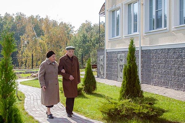 Пожилая пара гуляет по территории санатория под ручку.