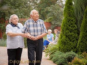 На фото пожилые мужчина и женщина под ручку гуляют на территории санатория.