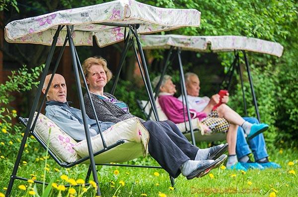 Пожилые люди качаются на садовых качелях в санатории Подмосковные вечера.