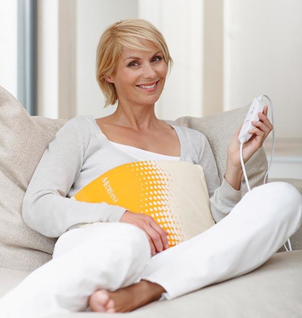 Женщина регулирует температурный режим электрической грелки.