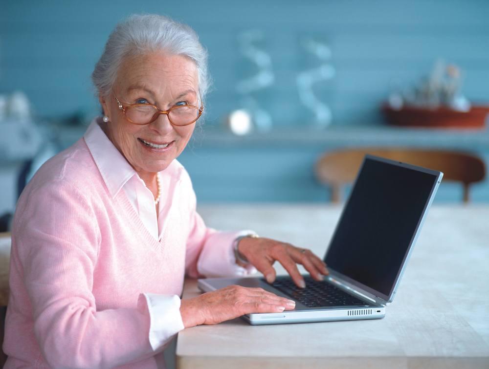 Пожилая женщина, пенсионер работает за компьютером.
