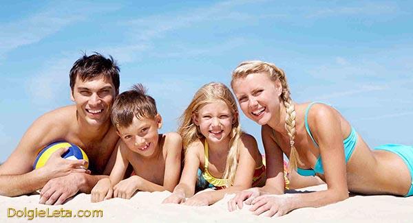 Родители с детьми загорают на море, лежат на песке.