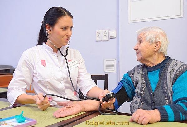 Замер давления у пожилой бабушке в медицинском кабинете.
