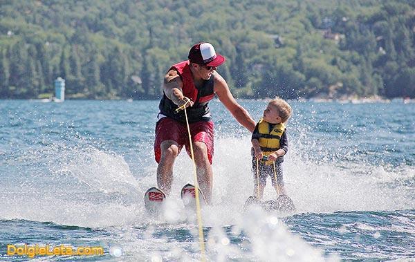 Папа с малышом катаются на водных лыжах.