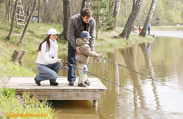 Семья с ребенком на рыбалке ловит рыбу.