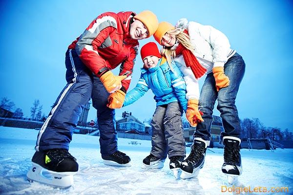 Семья с ребенком на катке катается на коньках.
