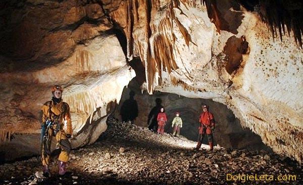 Спелеотуризм - семья изучает пещеру.