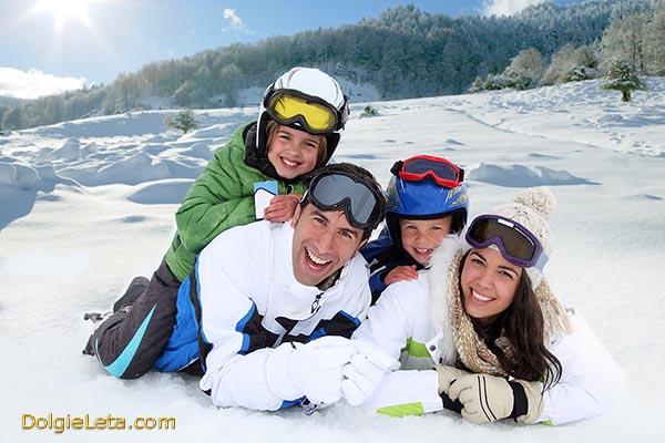 Счастливая семья лежит на снегу - о популярных видах активного семейного отдыха.