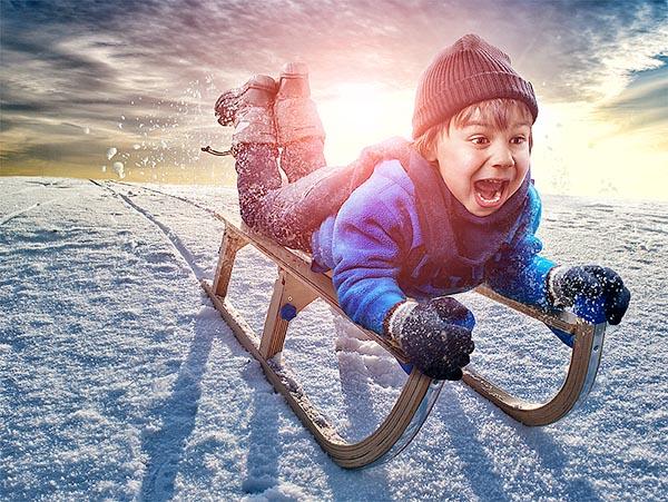 Безопасность зимних санок - маленький мальчик спускается со снежной горы лежа на санях.