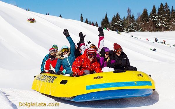 Веселая компания съезжает с горы в больших надувных зимних санках.