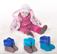 Детские зимние валенки различных размеров и малыш на фотографии.