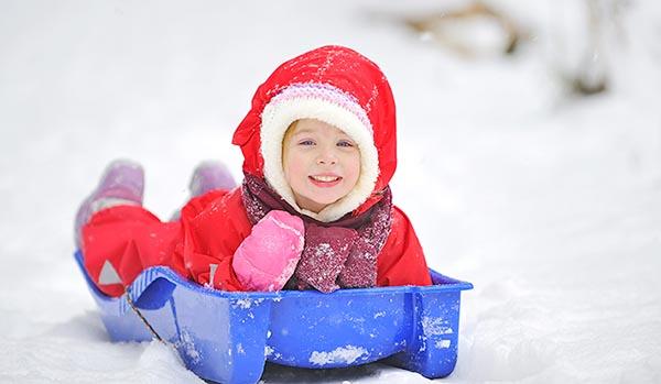 Счастливая девочка на пластиковых санках-корыто.