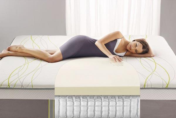Девушка, лежа, наслаждается ортопедическим матрасом - правильная и ровная осанка.